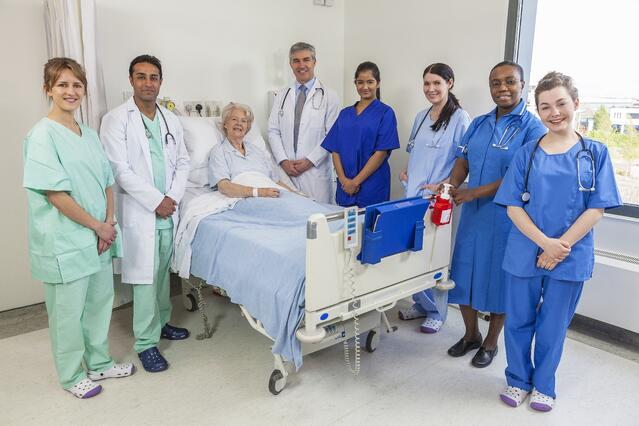 Group of nurses and doctors beside patient's bed to demonstrate Sutter Health and Scripps Health choosing Presagia software