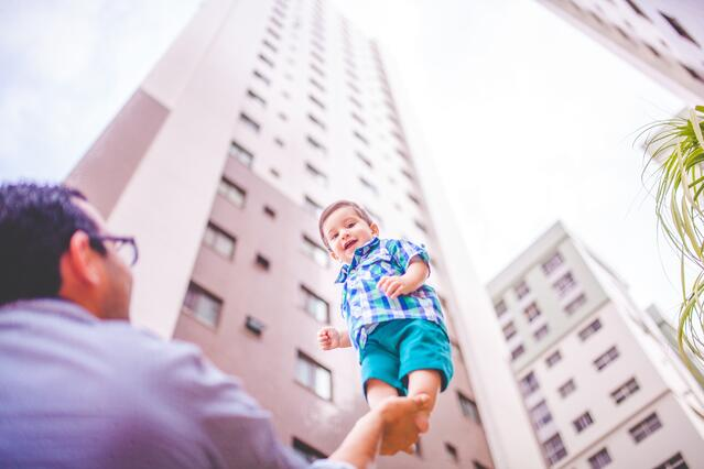 A New York father raises his infant son in the air