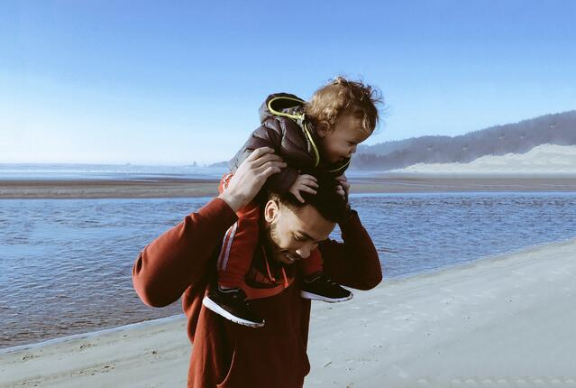 Happy father on gender neutral parental leave carries baby at the beach