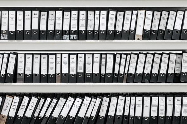 Shelves of consistently labelled binders that contain absence management information