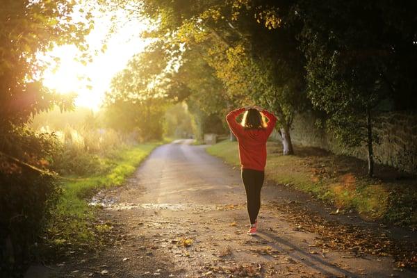 A healthy employee in jogging gear walks towards the setting sun on a trail